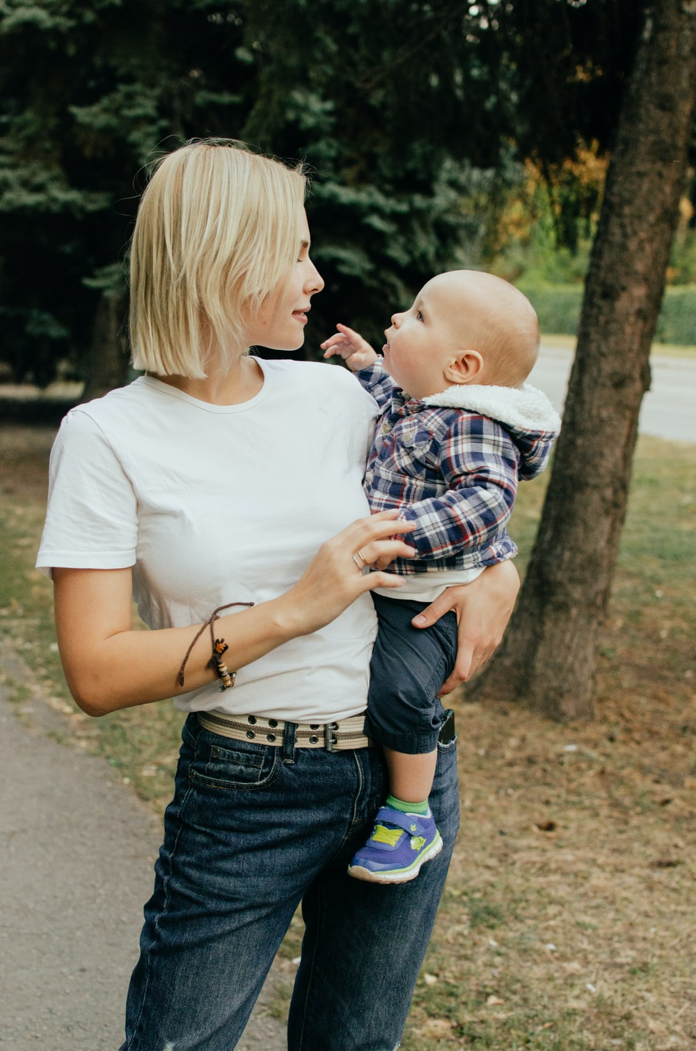 woman in white shirt carrying baby in blue and white plaid shirt