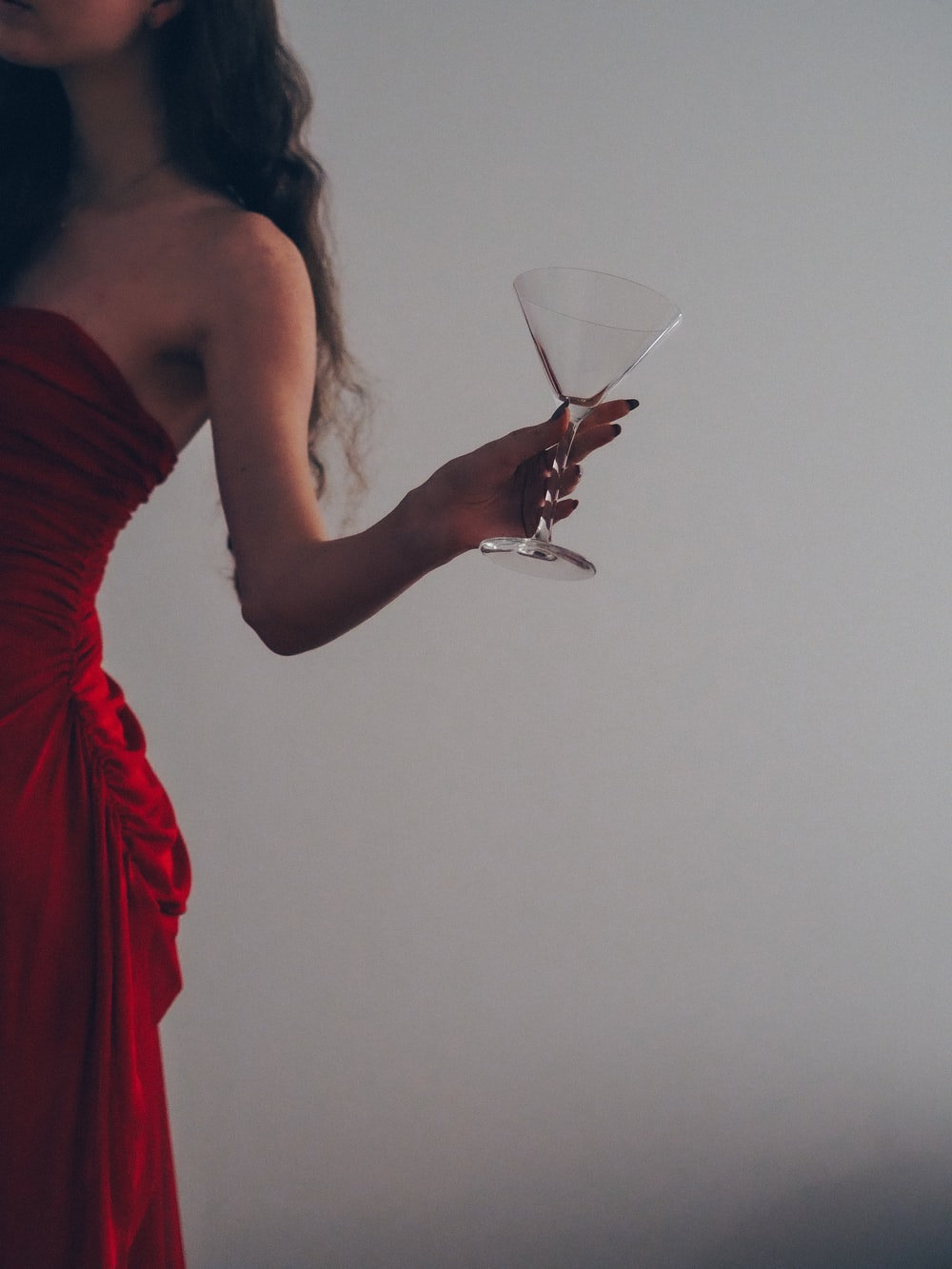 woman in red tube dress holding wine glass