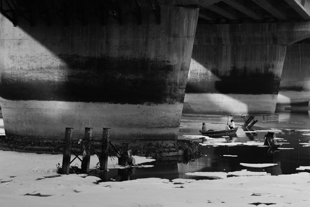 grayscale photo of people on beach near bridge