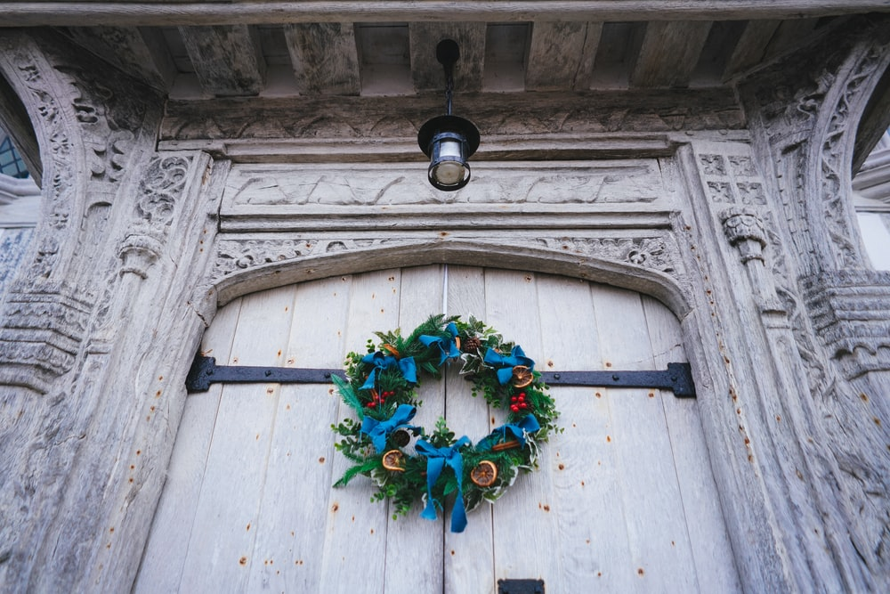 green red and yellow wreath on white wooden door