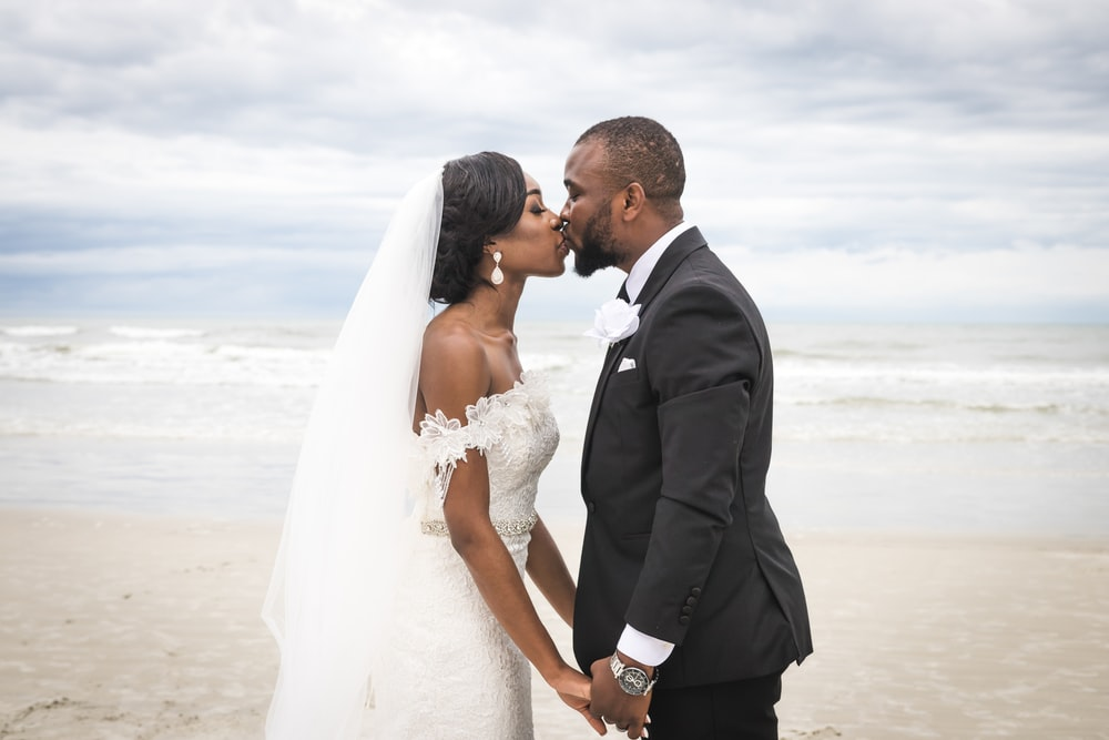 man in black suit kissing woman in white wedding dress on beach during daytime