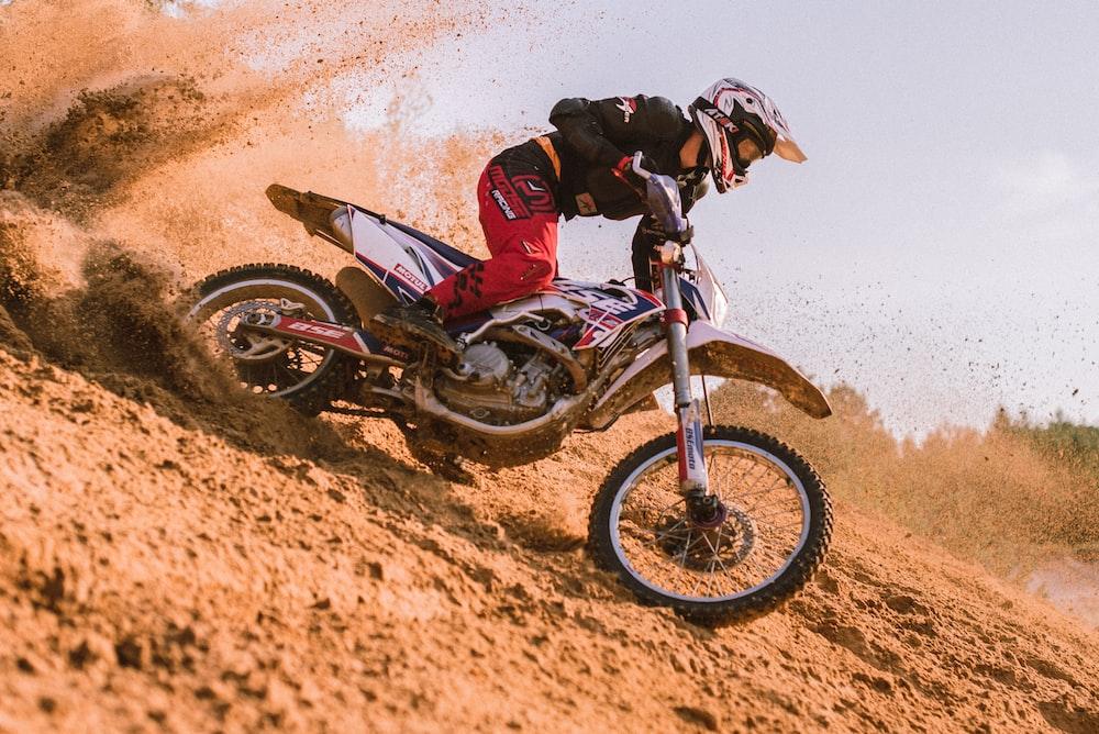 man in red and black motocross suit riding motocross dirt bike