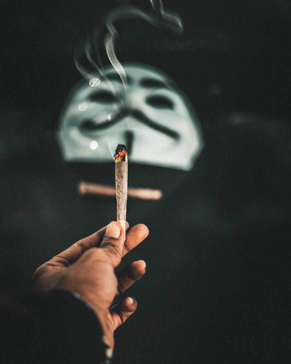 person holding cigarette stick with white smoke