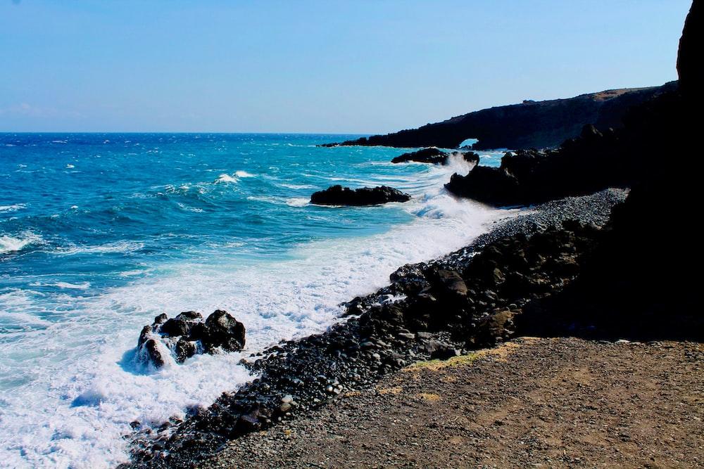 black rocks on seashore during daytime