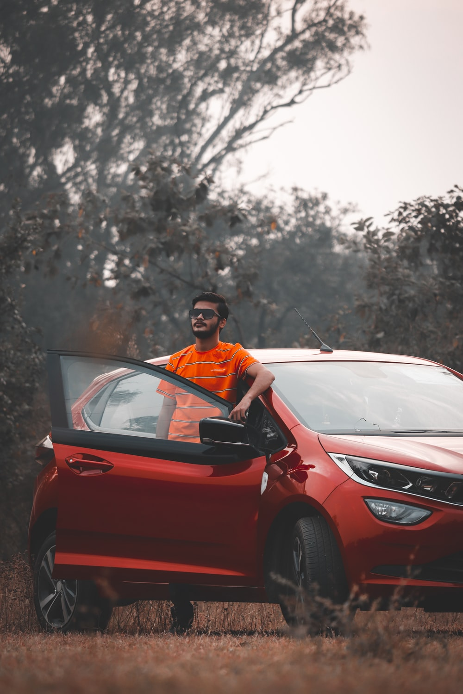 man in orange shirt driving red car