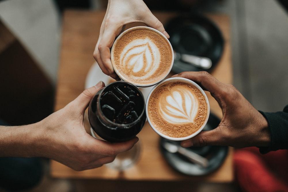person holding cappuccino in black ceramic mug