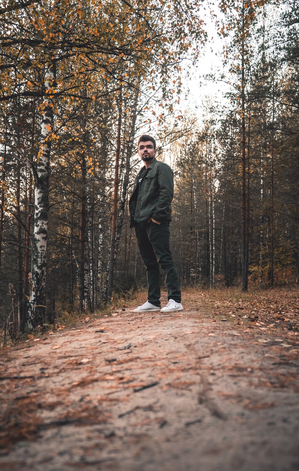 man in black jacket standing on brown dried leaves on forest during daytime