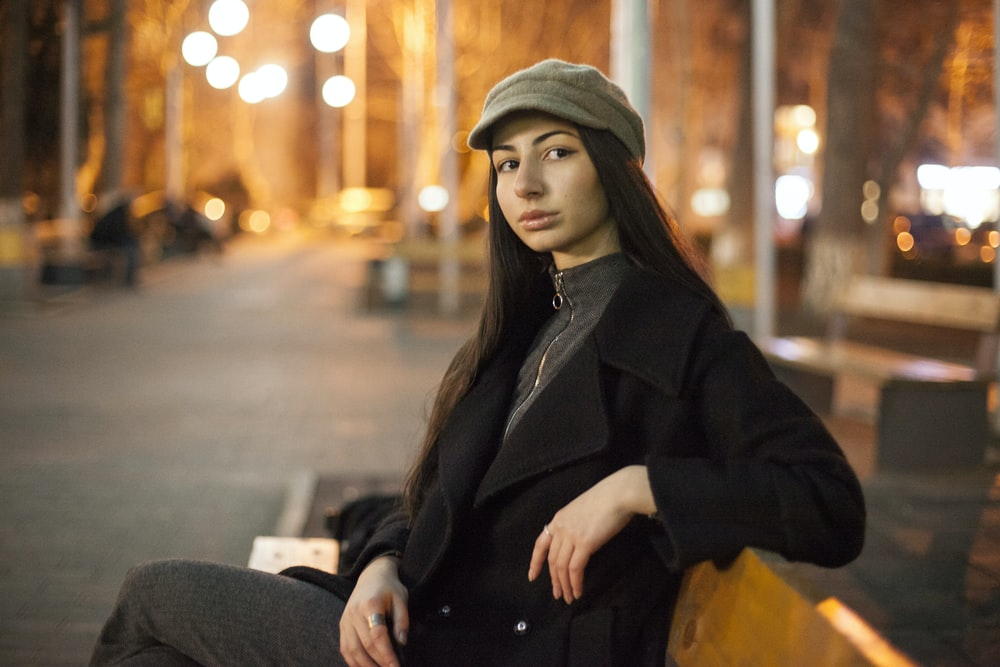 woman in black coat and brown hat sitting on bench during night time