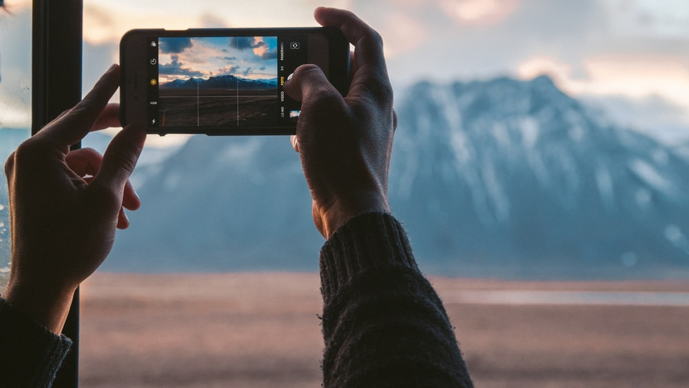 person holding black smartphone taking photo of mountain during daytime