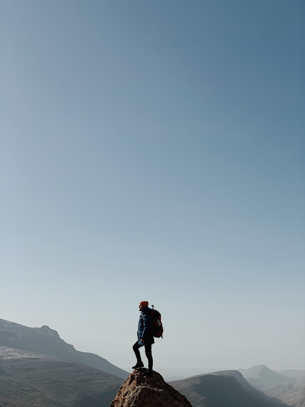 man in black jacket and black pants standing on top of mountain during daytime