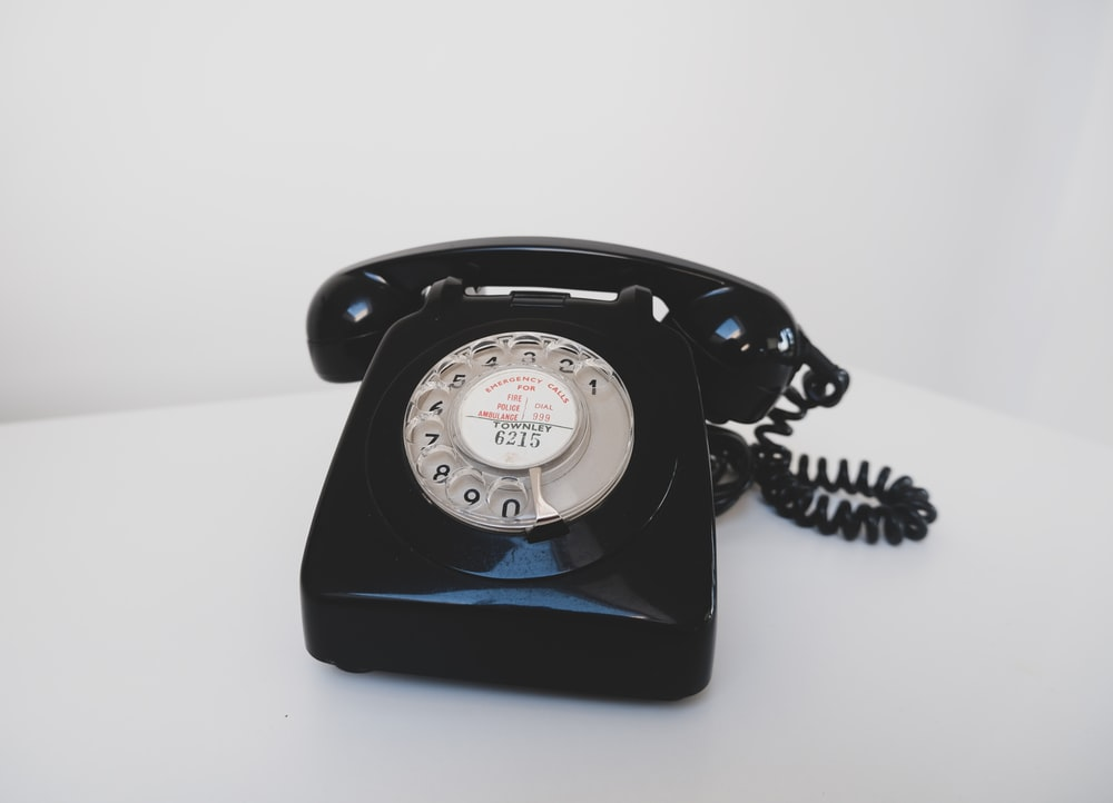 black rotary phone on white surface