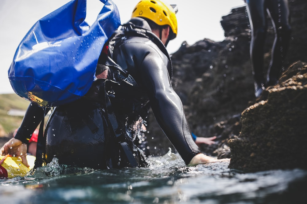 man in black wet suit wearing yellow helmet in blue water during daytime