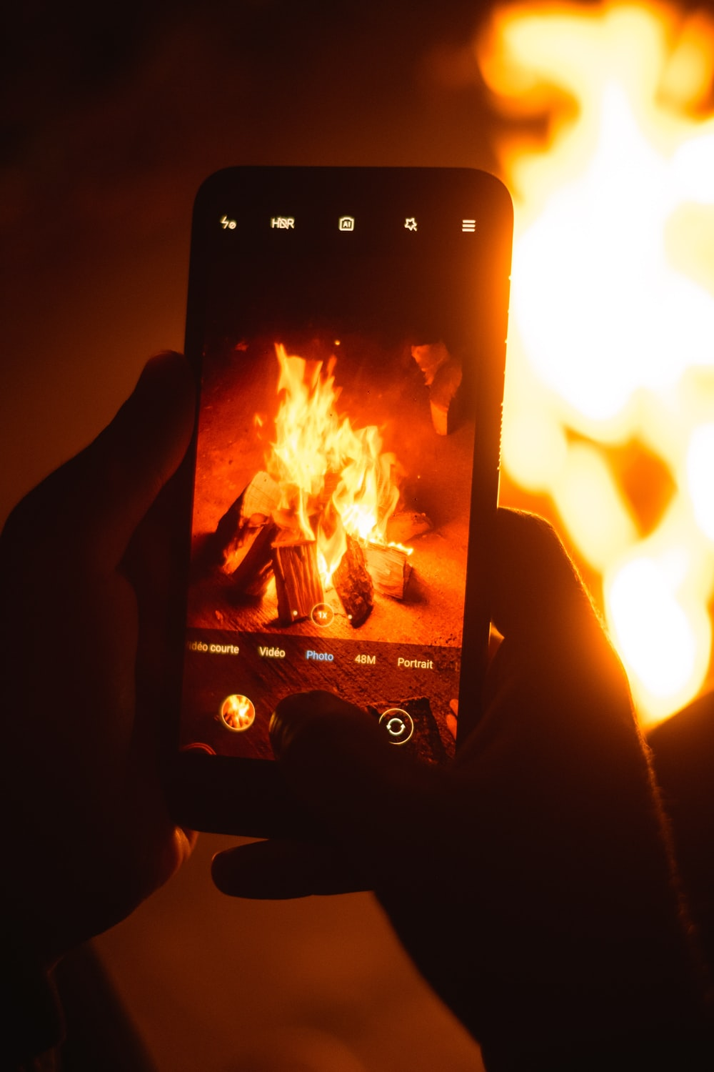 person holding black smartphone showing fire