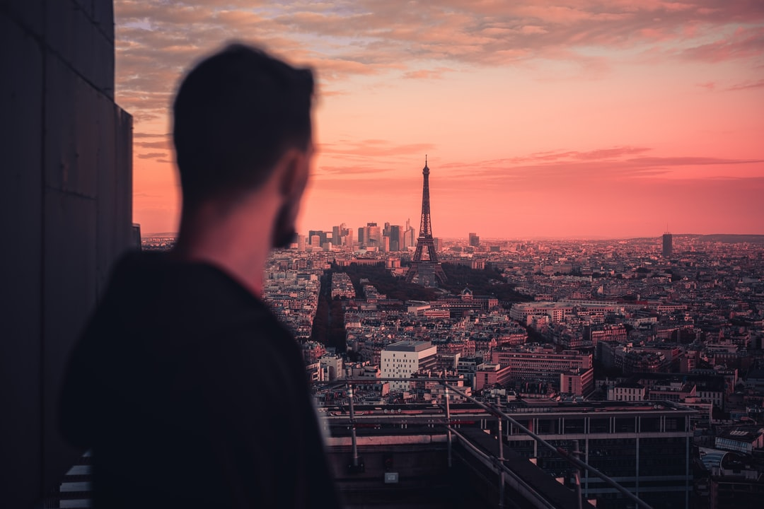 Man In Black Jacket Looking At City Buildings During Sunset - unsplash