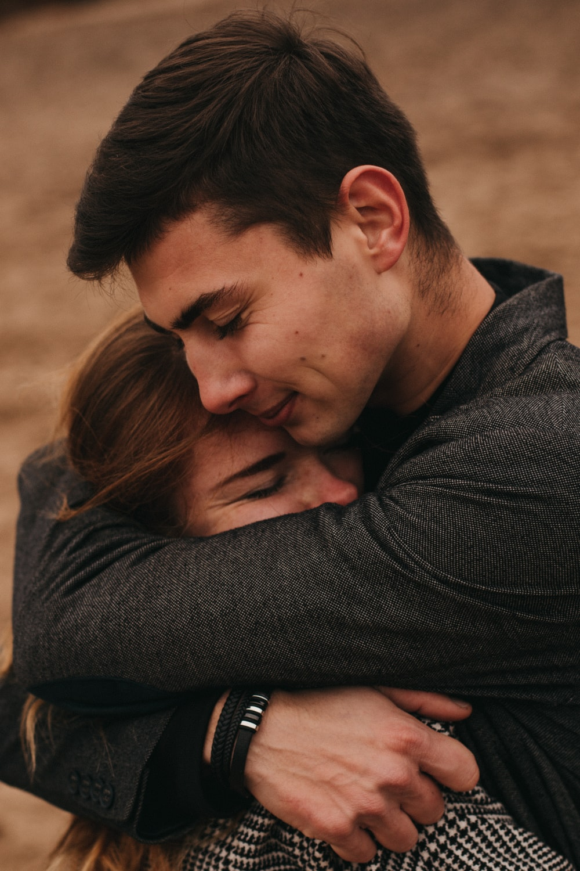 man in black long sleeve shirt hugging woman in black long sleeve shirt