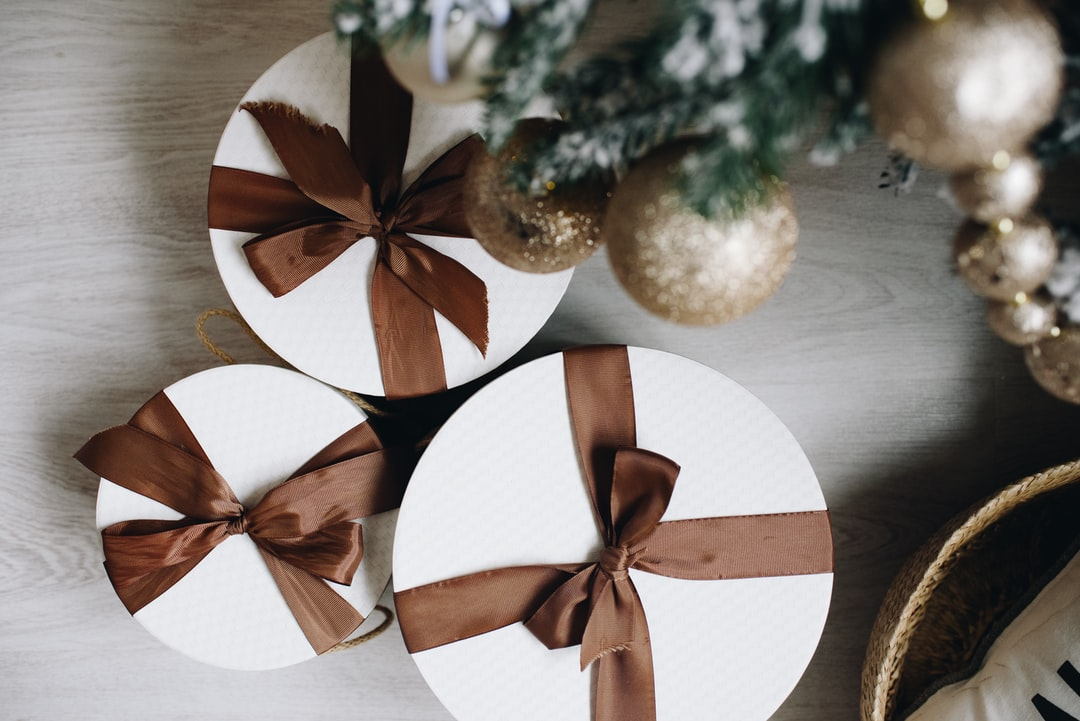 Top View If Elegant Gift Boxes With Ribbon Bows. Packed Christmas Presents Under the Christmas Tree. - unsplash