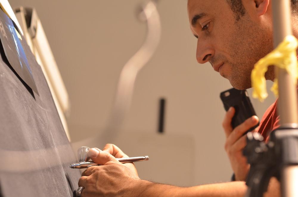 man in black shirt writing on white paper