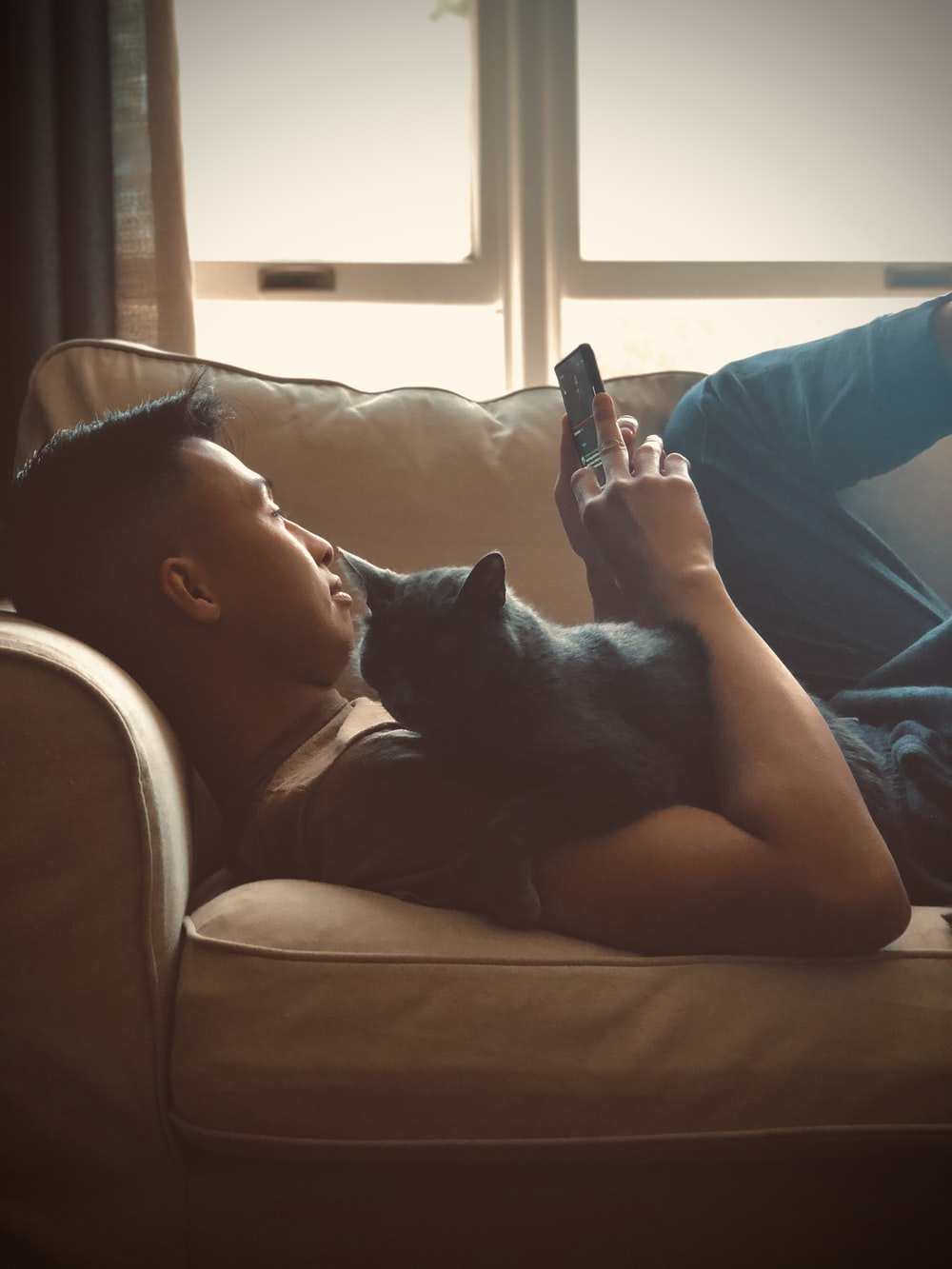 woman in blue tank top lying on couch with black cat