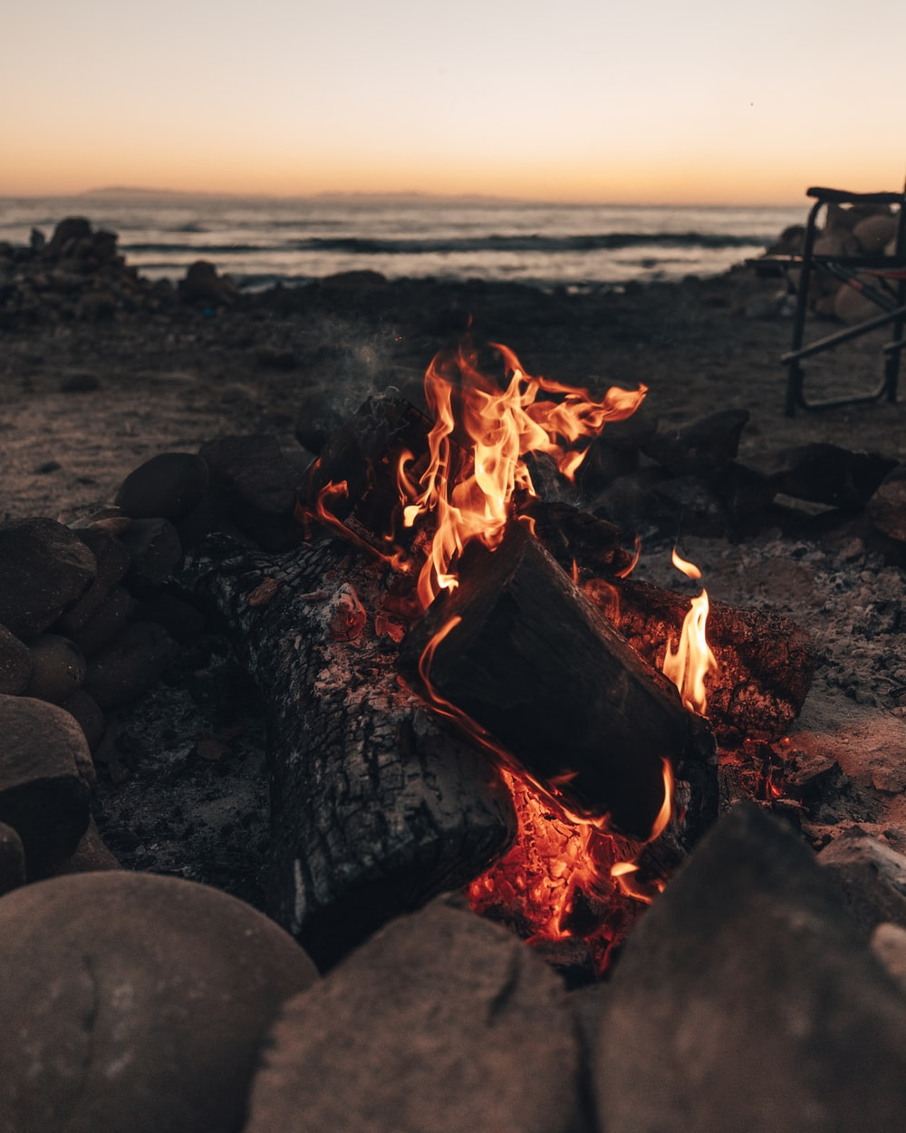 burning wood on the beach during sunset