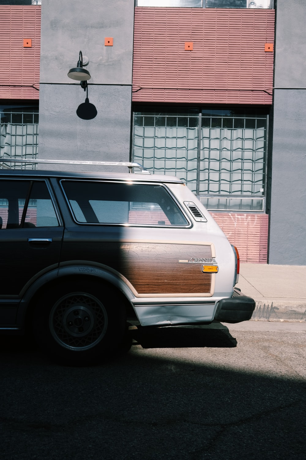brown station wagon parked beside red and white building