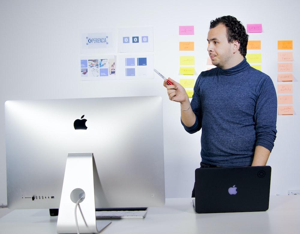 man in blue crew neck t-shirt holding black laptop computer