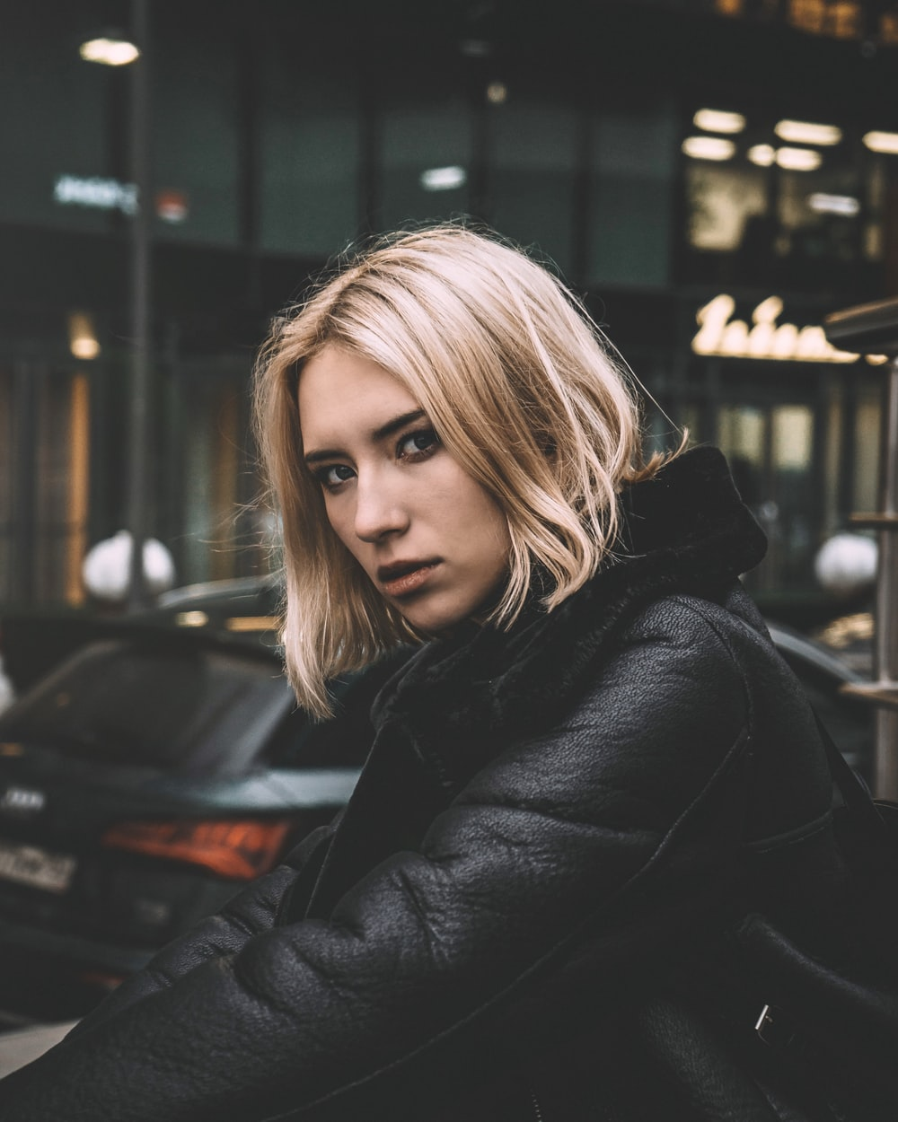 woman in black leather jacket standing near black car during night time