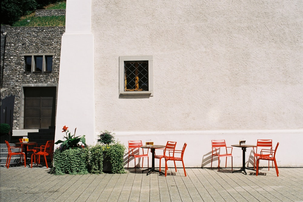 red and brown wooden chairs and table near white concrete wall