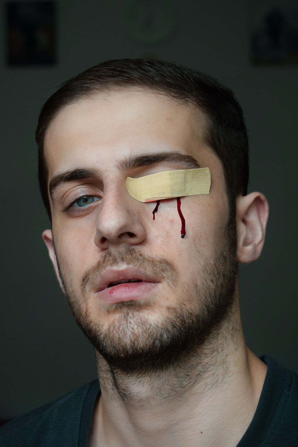 man with brown band aid on his mouth