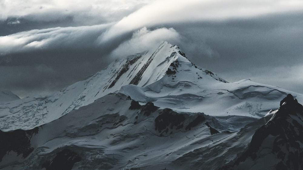 snow covered mountain under white clouds