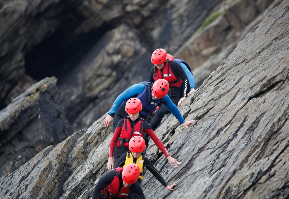 2 women in red and blue suit climbing on brown rock