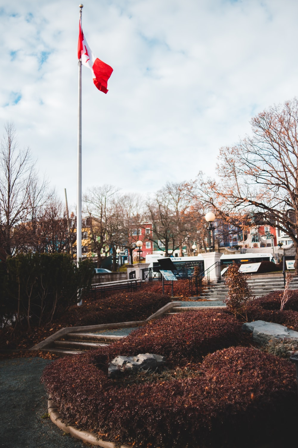 white and red flag on pole near bare trees during daytime