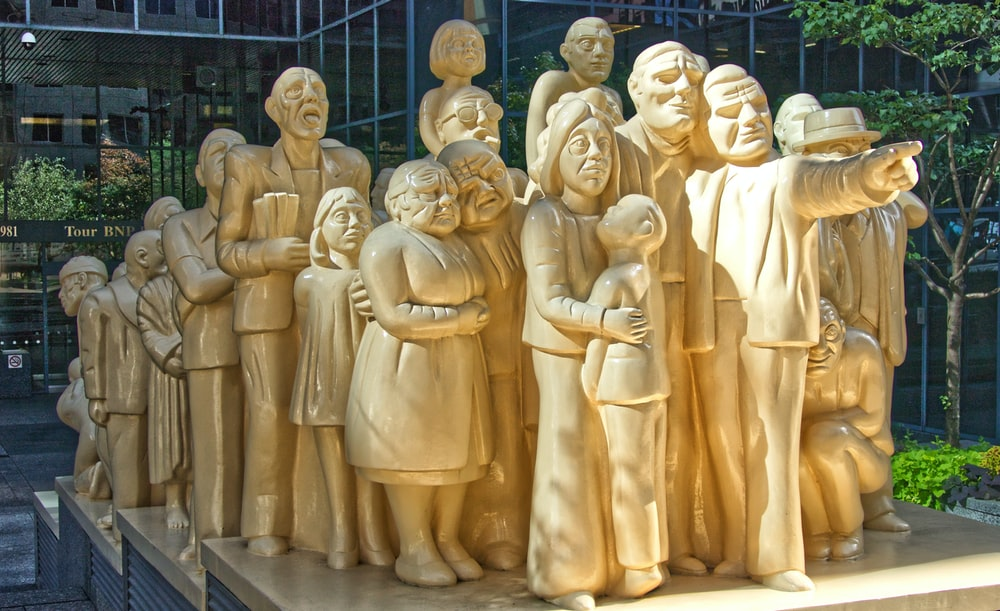 gold statue of people during daytime