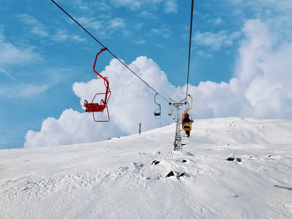 person in yellow jacket and black pants riding on cable car over snow covered ground during