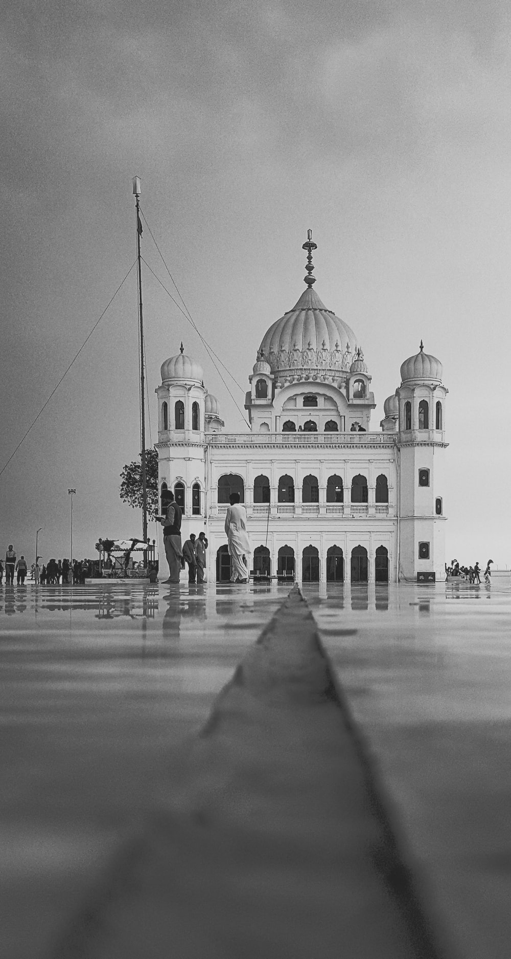 grayscale photo of people walking near dome building