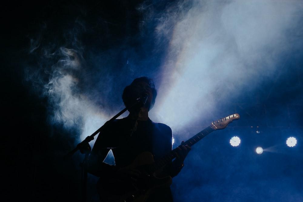 woman in black tank top playing guitar