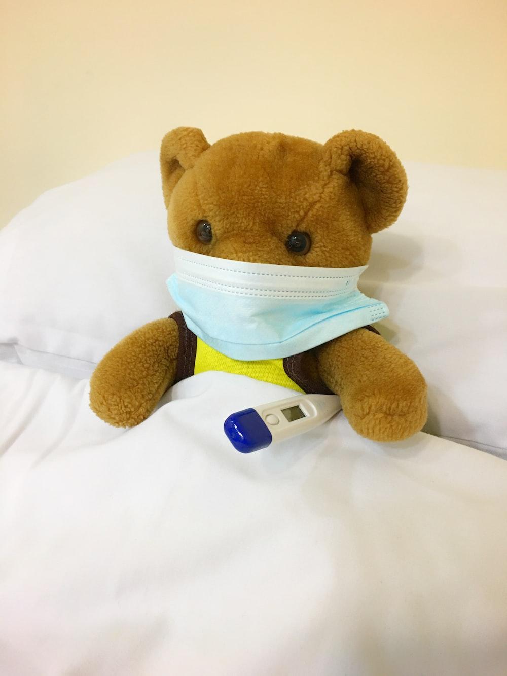 brown bear plush toy on white textile
