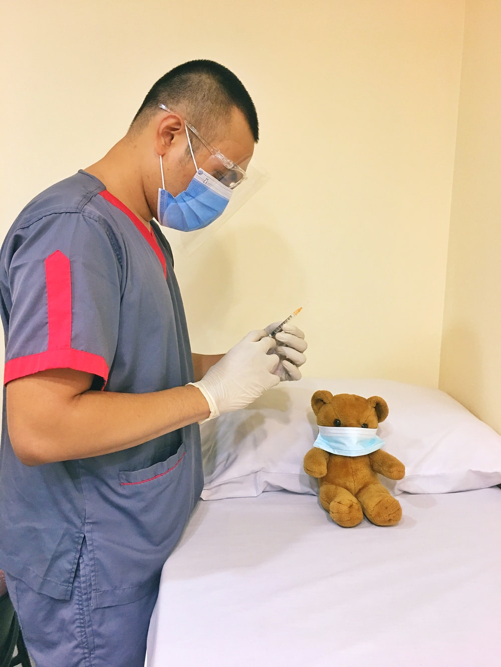 man in blue and red polo shirt holding a pen and a brown bear plush toy