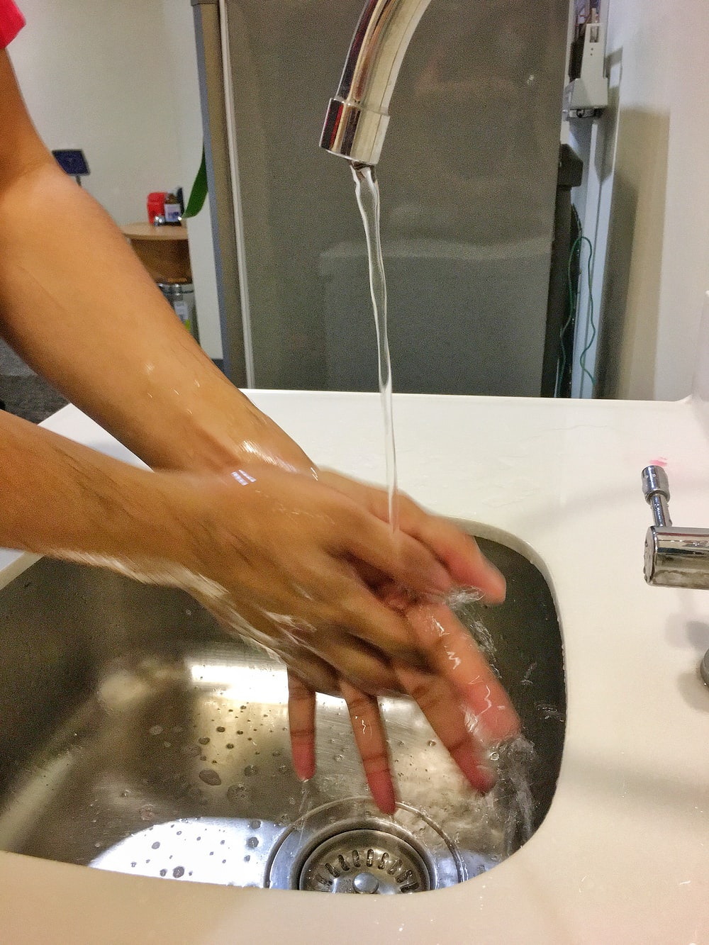 person washing hand on sink