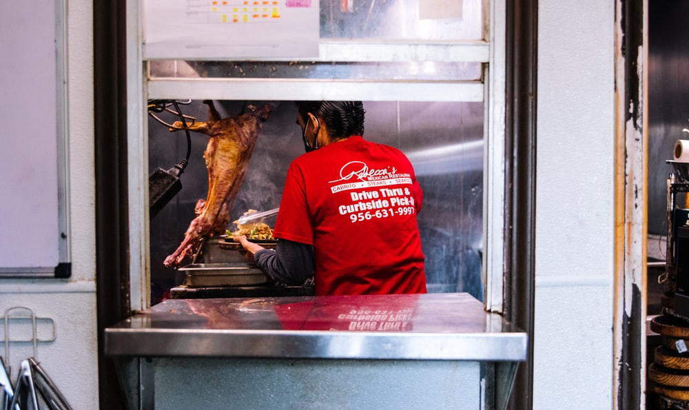 man in red hoodie sitting in front of cooked chicken