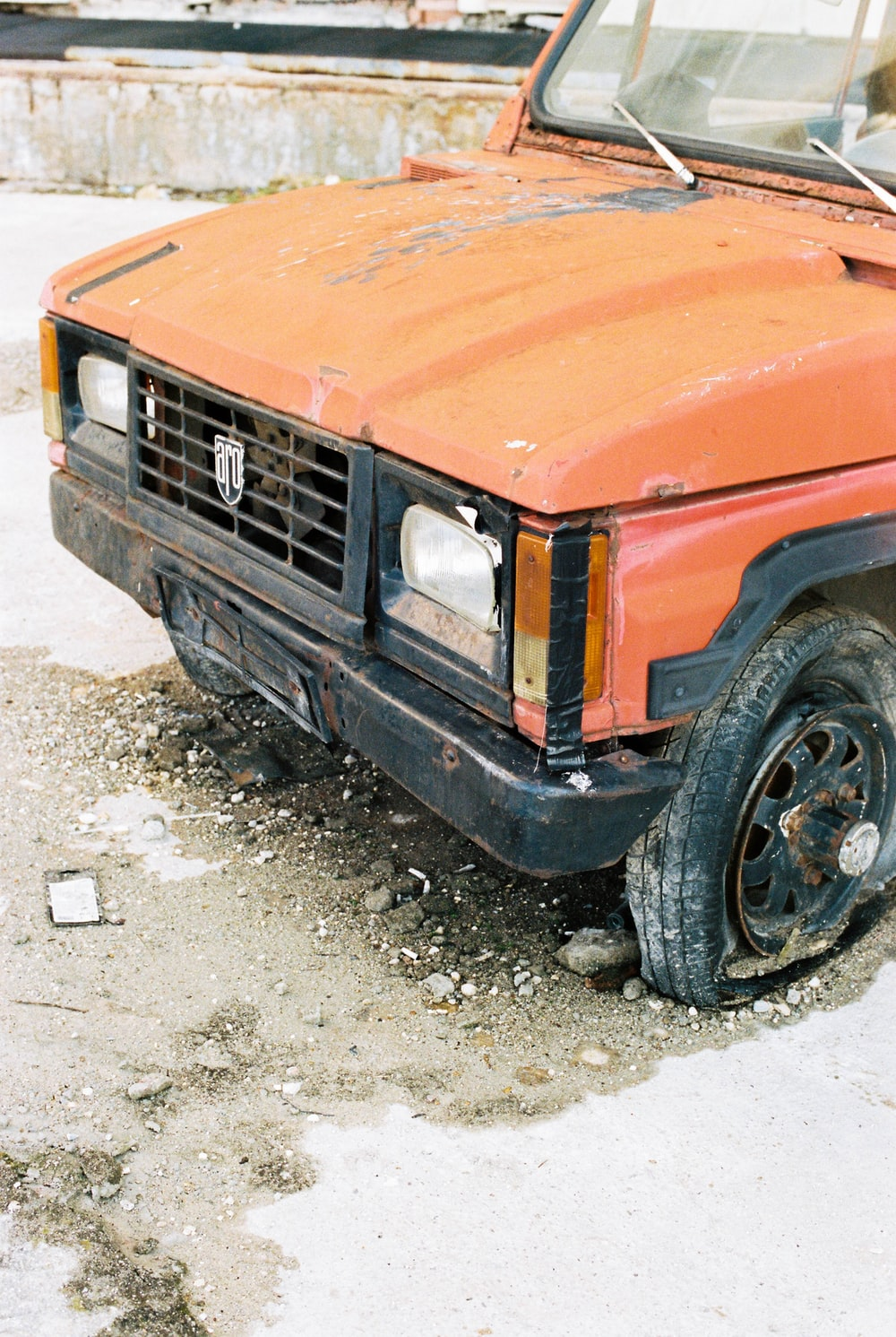 orange car on gray dirt ground