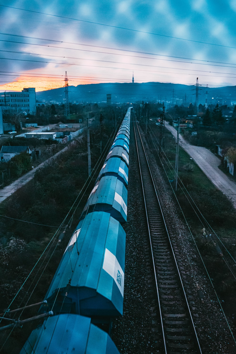 blue and white train on rail tracks during daytime