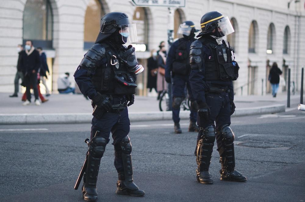 2 men in black and white helmet and black helmet walking on street during daytime