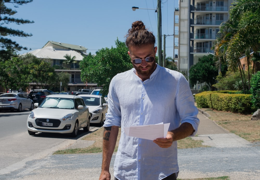 man in white button up t-shirt holding white printer paper