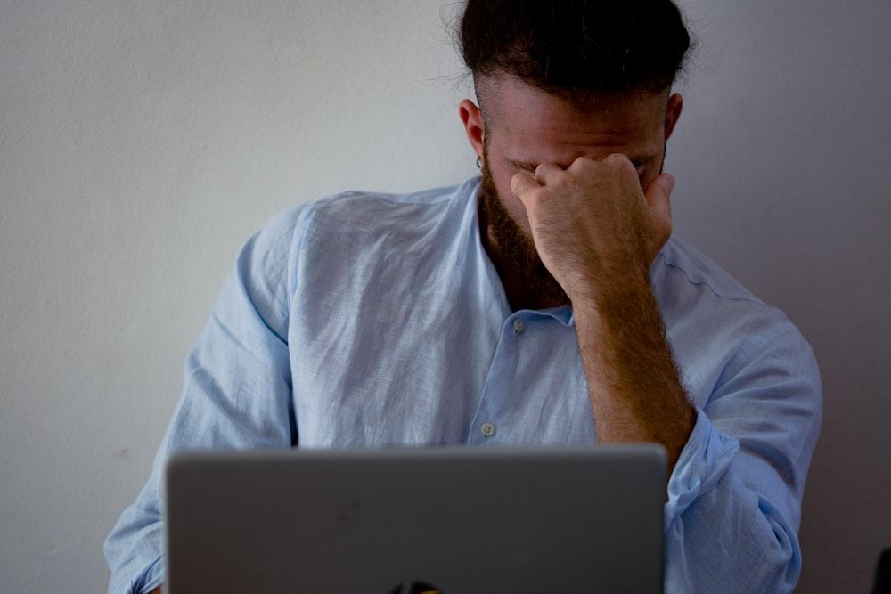 man in blue dress shirt holding silver macbook
