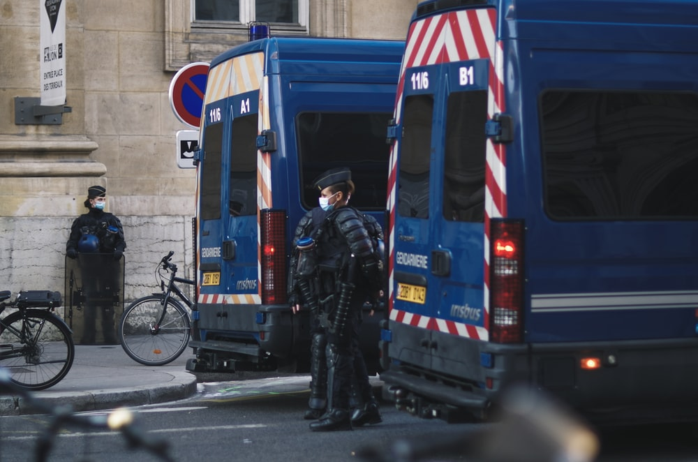 man in black jacket standing beside blue and white bus during daytime