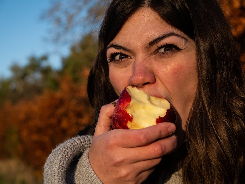 woman in gray sweater holding sliced of apple