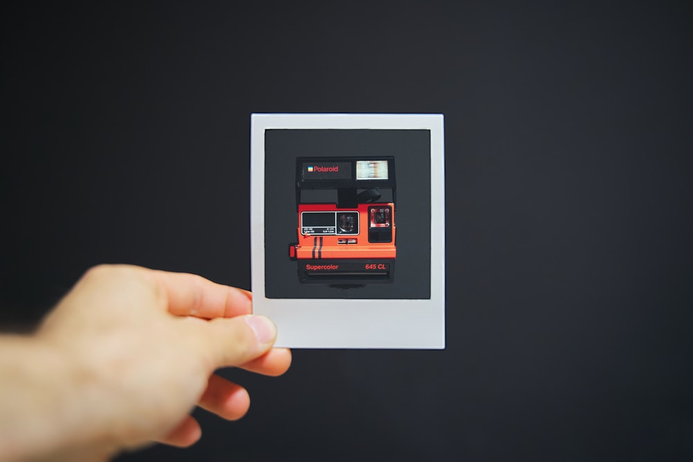 person holding white picture frame