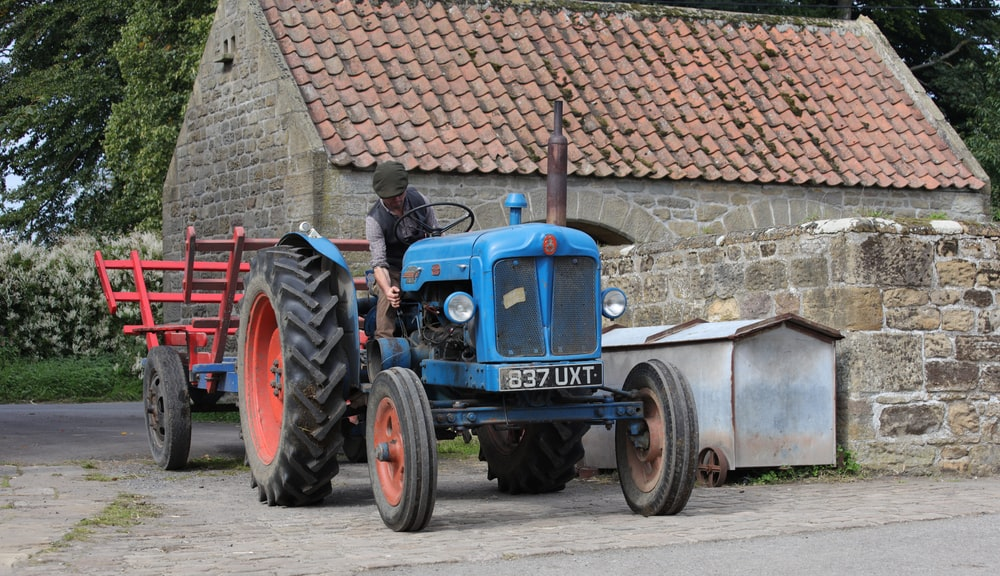 blue tractor parked beside brick wall