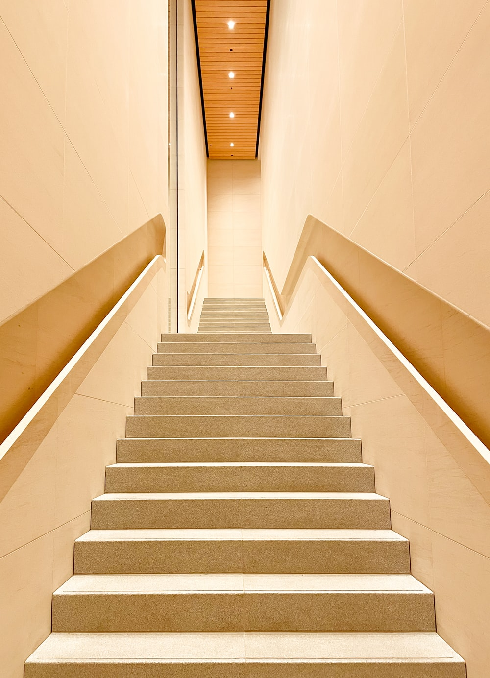 white concrete staircase with stainless steel railings