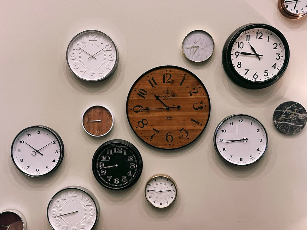 white and brown analog wall clock at 10 00